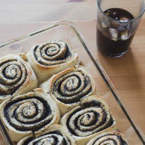 Eine Ofenform gefüllt mit veganen Mohnschnecken und daneben ein schwarzer Eiskaffee in einem Glas.