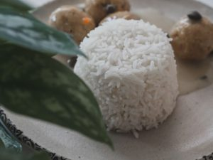 Auf einem Teller steht hübsch ein kleines Türmchen aus Reis neben der Kapernsauce.