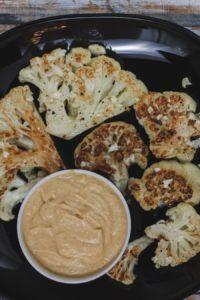 Ein schwarzer Teller mit gerösteten Blumenkohl-Scheiben und einem Schälchen mit veganem Käsedip