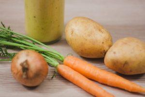 Zwei Karotten, eine Zwiebel und zwei Kartoffeln auf einem Tisch