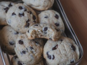 Ein angebissener veganer Keks in einer vollen Keksdose